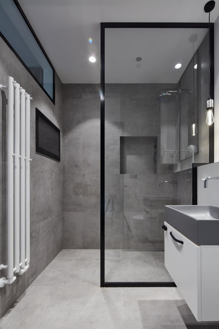 In deze kleine stoere badkamer zijn gekozen voor dezelfde betonlook tegels voor de vloer en de wanden.
