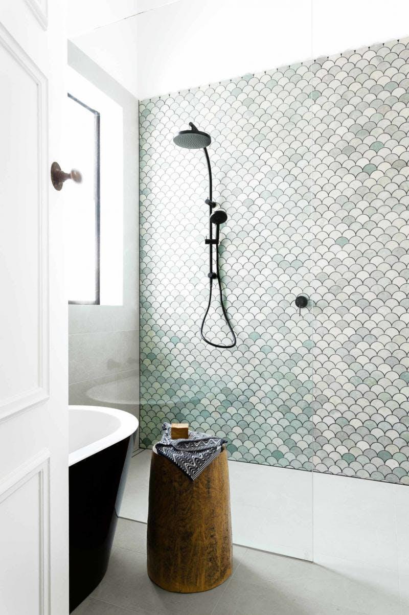 De accentmuur met mooie groene schubben tegels steelt de show in deze badkamer.