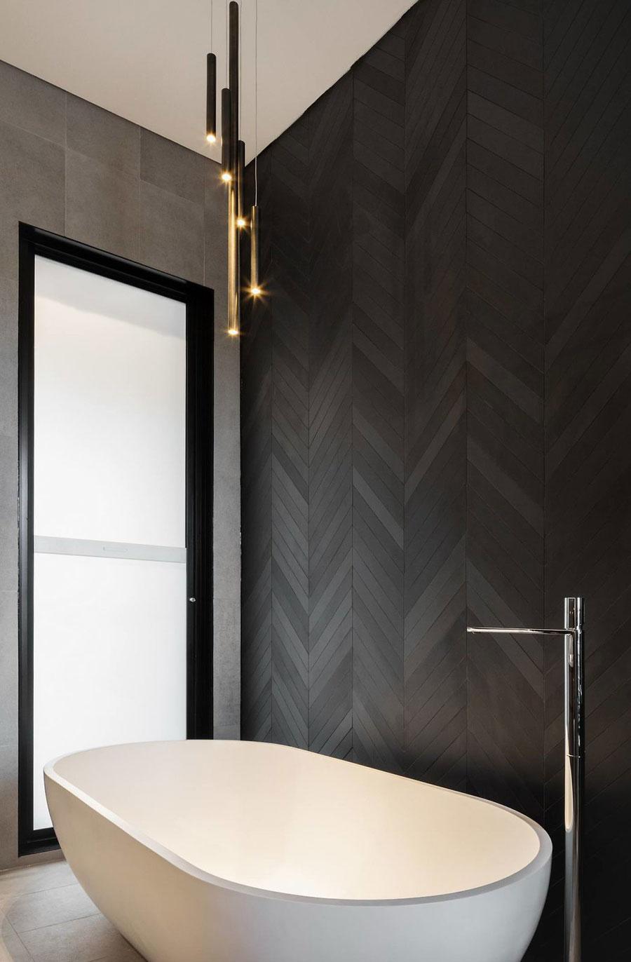 In deze chique moderne badkamer is een accentmuur gecreëerd met luxe bruine visgraat wandtegels.