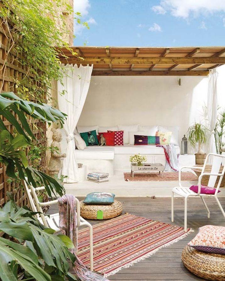 Een super leuk bohemian dakterras in Barcelona, met vrolijke en kleurijke kussens en vloerkleden.
