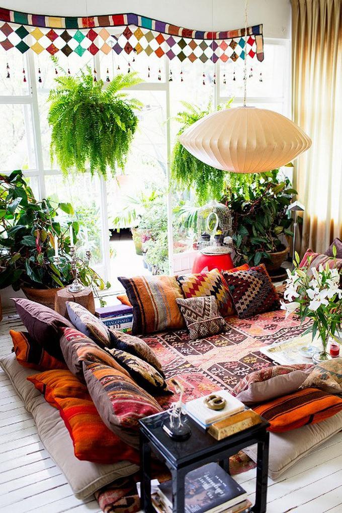 Een gezellige boho zithoek met grote en kleurrijke kussens en kleden op de vloer.