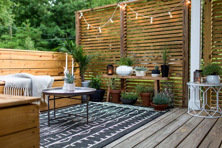 Den leuke bohemian stijl tuin van Megan & Mike is super gezellig ingericht met een groot vloerkleed, een Marokkaans tafeltje, verschillende leuke plantjes en slingerverlichting aan de houten schutting.