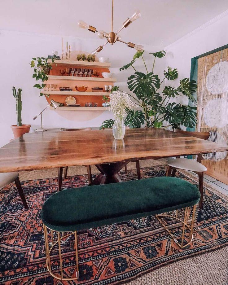 Mooie boho eethoek met boomstam eettafel, met daaromheen een mix van eetkamerstoelen en een chique groene fluwelen eetbank.