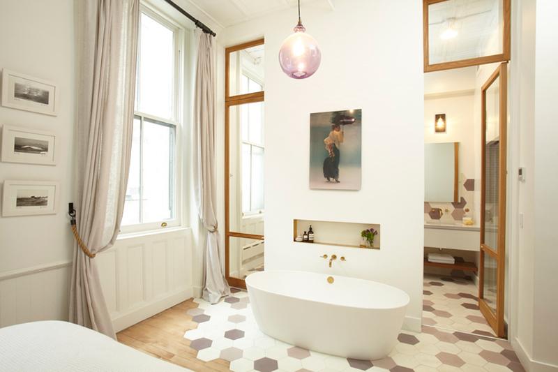 Chique badkamer met vrijstaand bad in slaapkamer