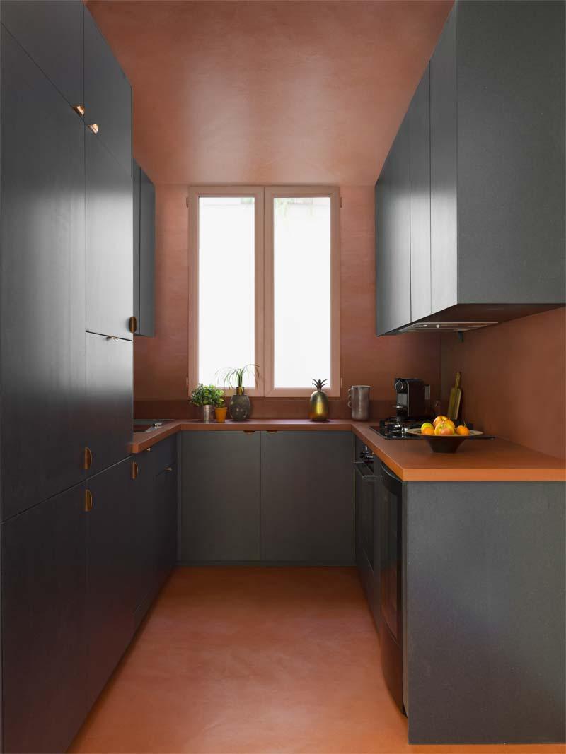 colour blocking keuken donkergrijze kasten zachtrode achtergrond