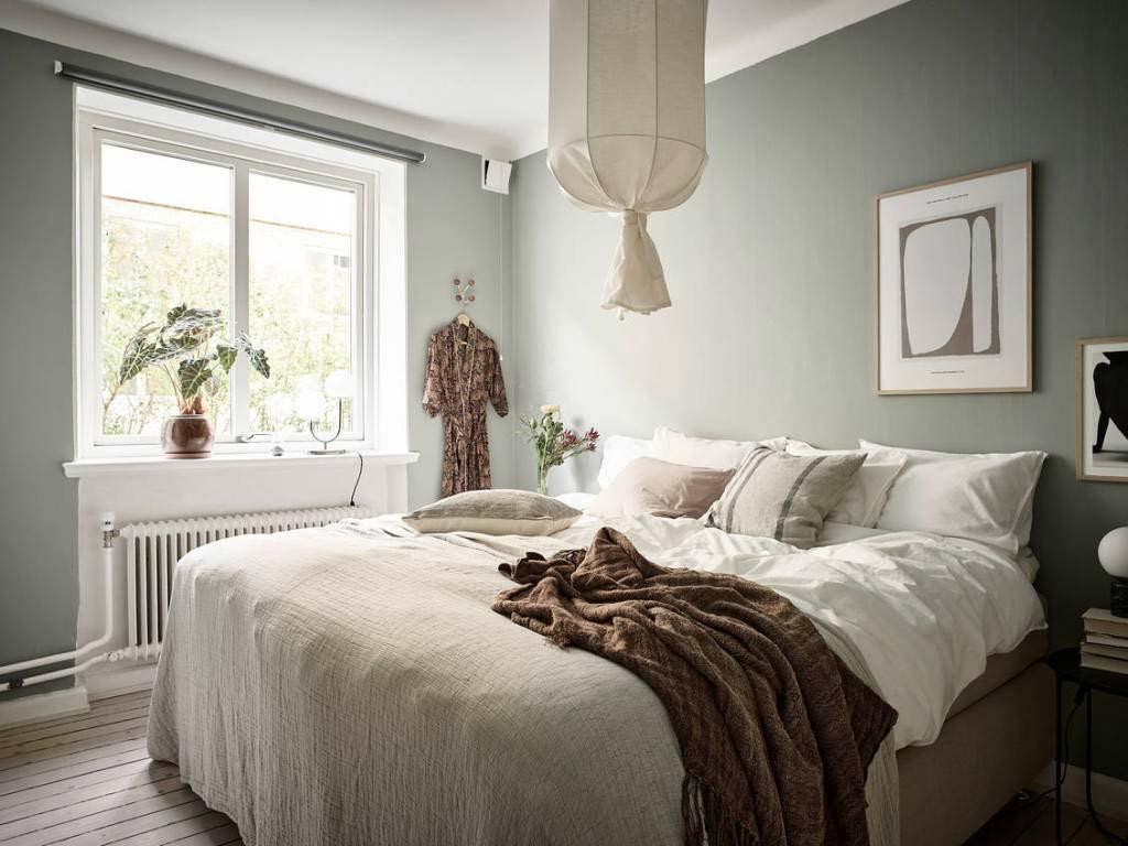 De muren in deze groene slaapkamer zijn geverfd in een mooie zachtgroene muurverf.