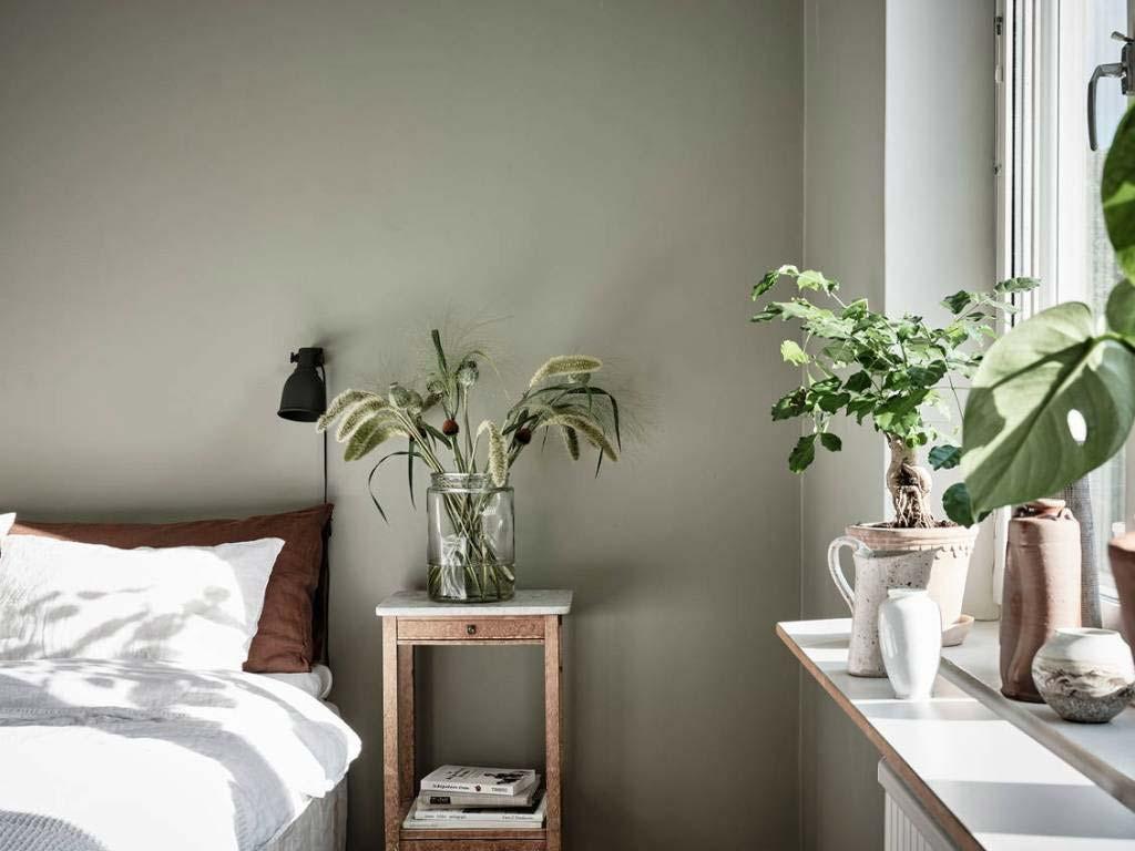 Zien de plantjes op het nachtkastje en de vensterbank in deze groene slaapkamer met groene muren er niet geweldig uit?