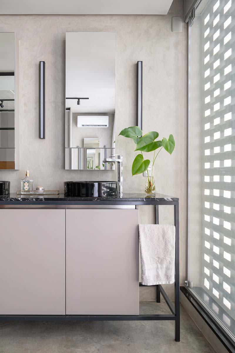 Betonlook in stoere badkamer met zwarte wastafels op marmeren blad