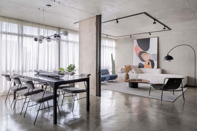 Stoere betonnen scheidingswand in industriele woonkamer met betonnen vloer en plafond