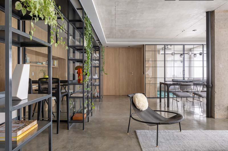 Betonnen vloer en plafond gecombineerd met stalen boekenkast en houten wandbekleding