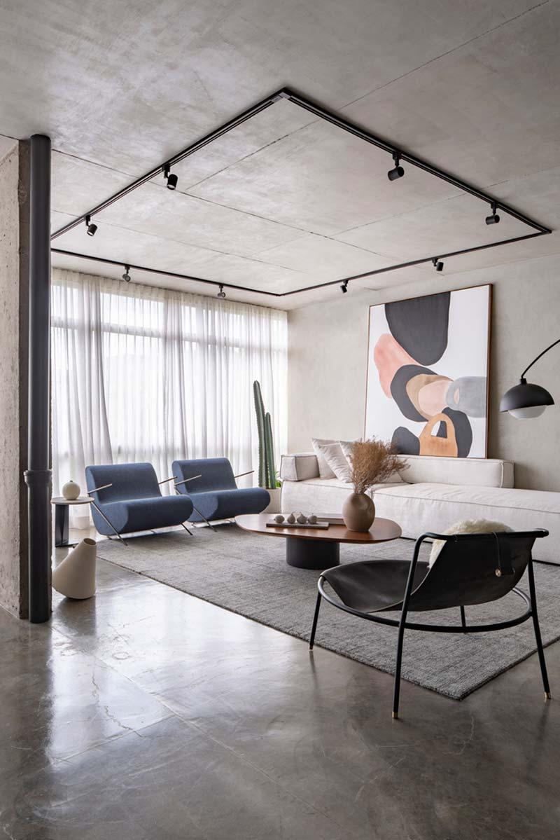 In deze industriele woonkamer is er gekozen voor een betonnen vloer, plafond en wanden