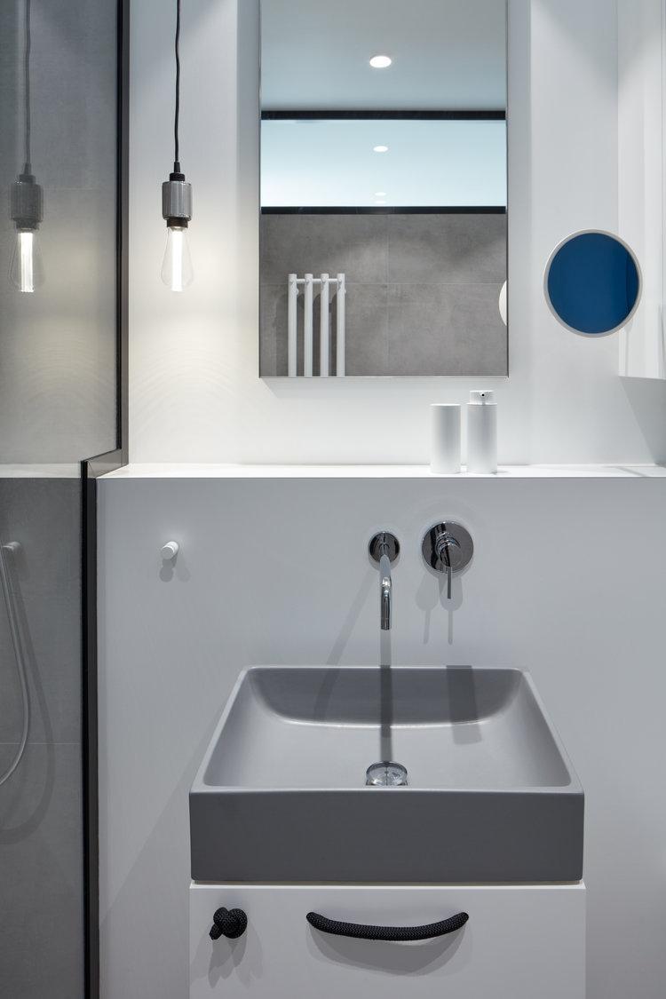 In deze kleine stoere badkamer kan je TV kijken vanuit de douche!