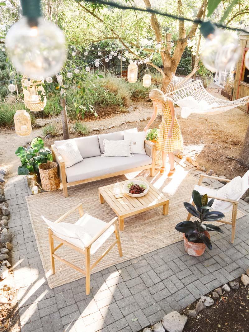 Het grote jute tuinkleed in de mooie tuin van Hannah past perfect bij de houten meubels.