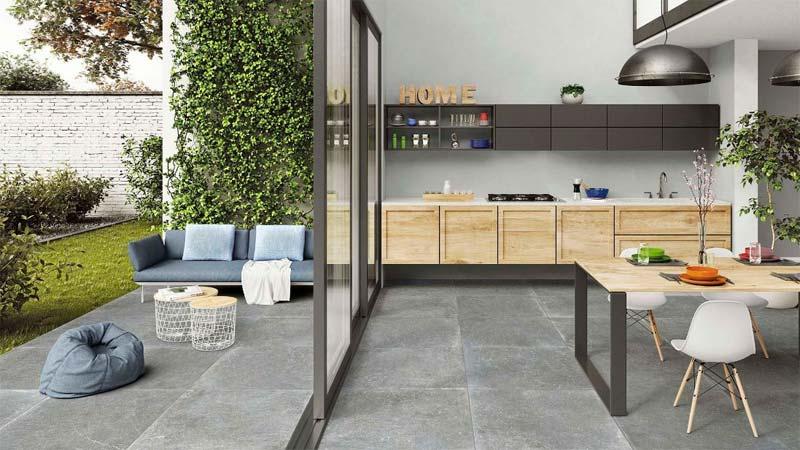 Door te kiezen voor dezelfde stoere keramische tegels voor de keuken en het terras in de tuin, wordt de tuin bij de keuken betrokken.