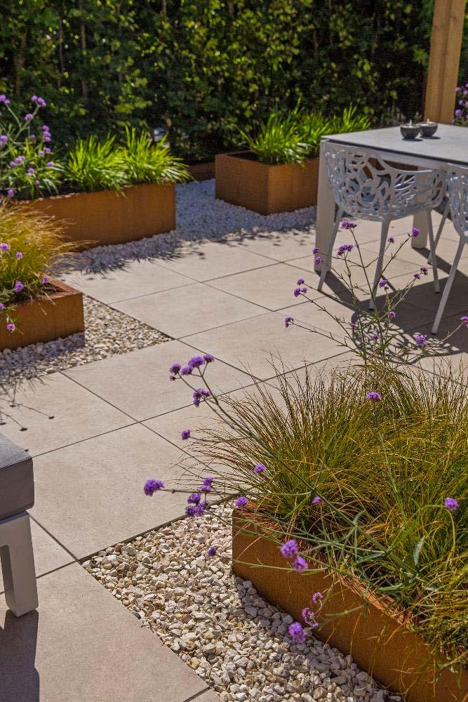 In deze moderne romantische tuin is er gekozen voor een combinatie van de keramische tegels Cerasolid Ultramoderno van 60x60x3 cm, grind en cortenstalen plantenbakken.