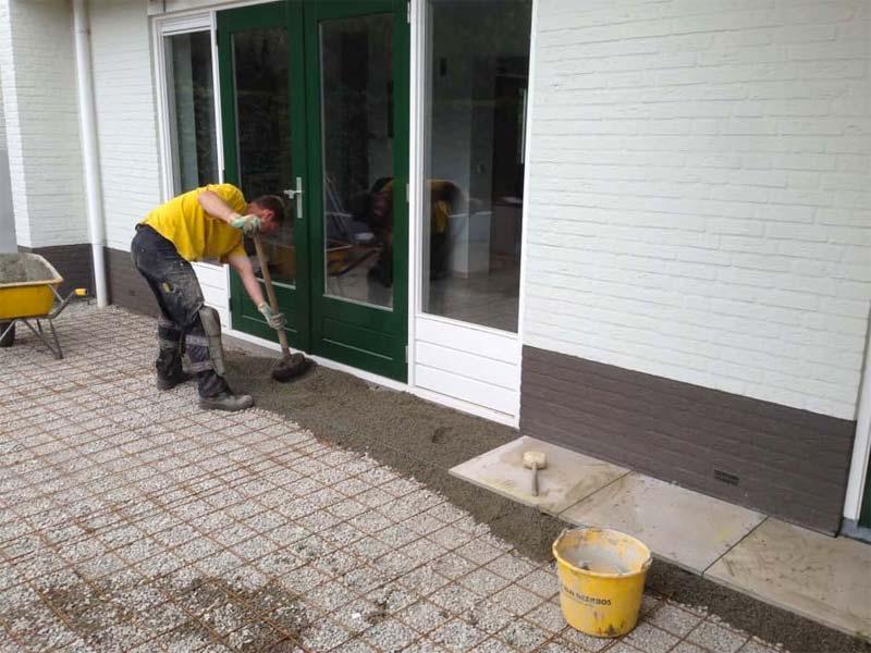 A. van Spelde hoveniers aan het werk in een tuin met het aanleggen van een terras met keramische tuintegels.