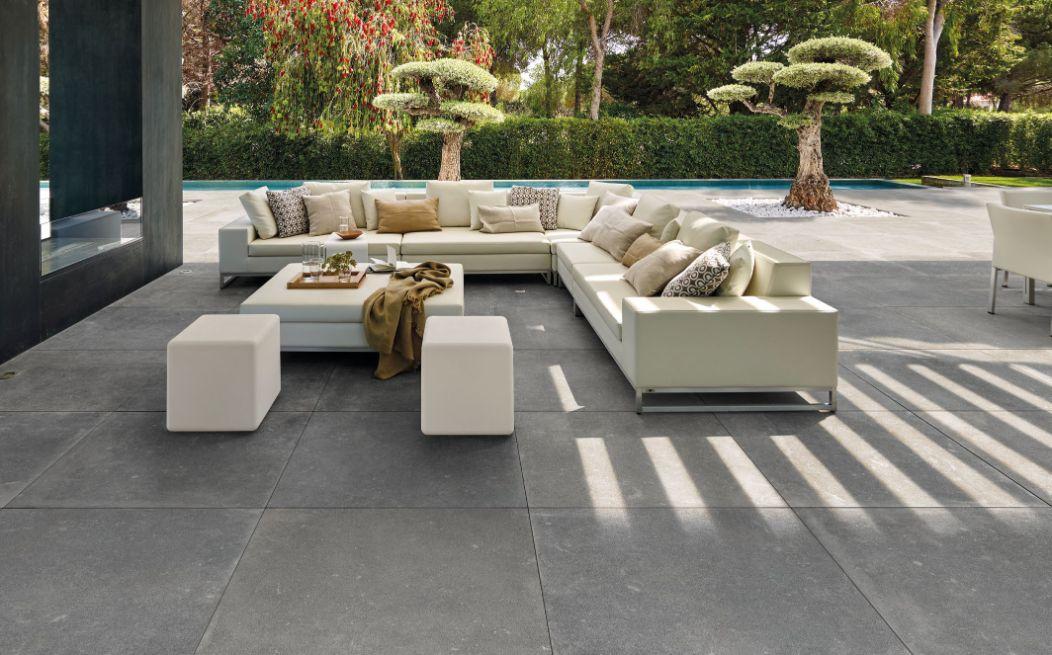In deze luxe moderne tuin is het grootste deel bestraat met grote grijze keramische tuintegels van het Italiaanse merk Kronos.