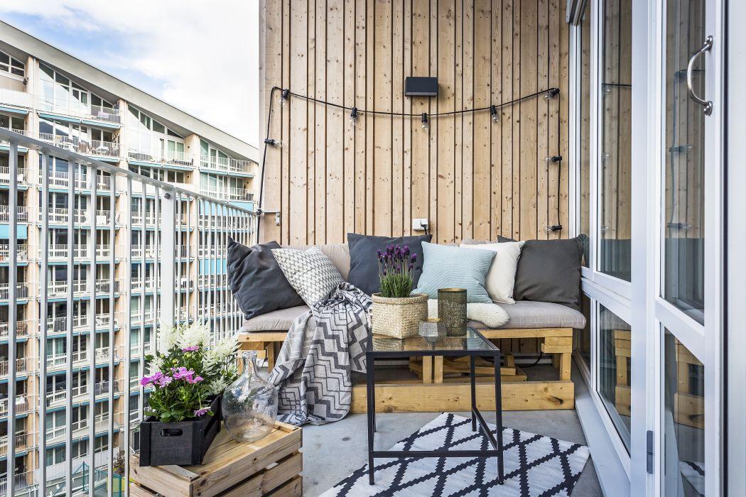 Klein balkon inrichten betonnen vloer en houten wandbekleding