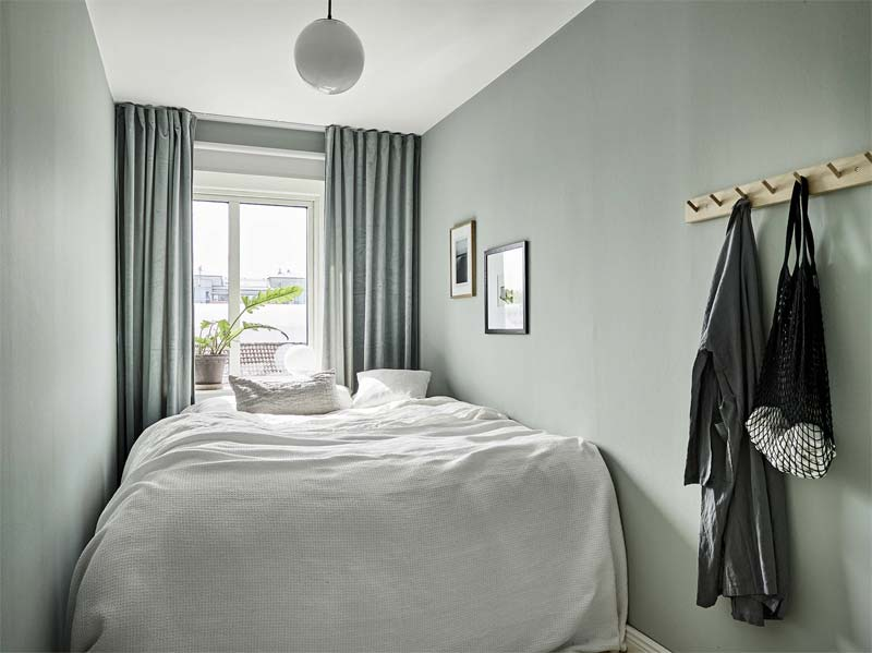Kleine groene slaapkamer met groene muren en mooie groene gordijnen.