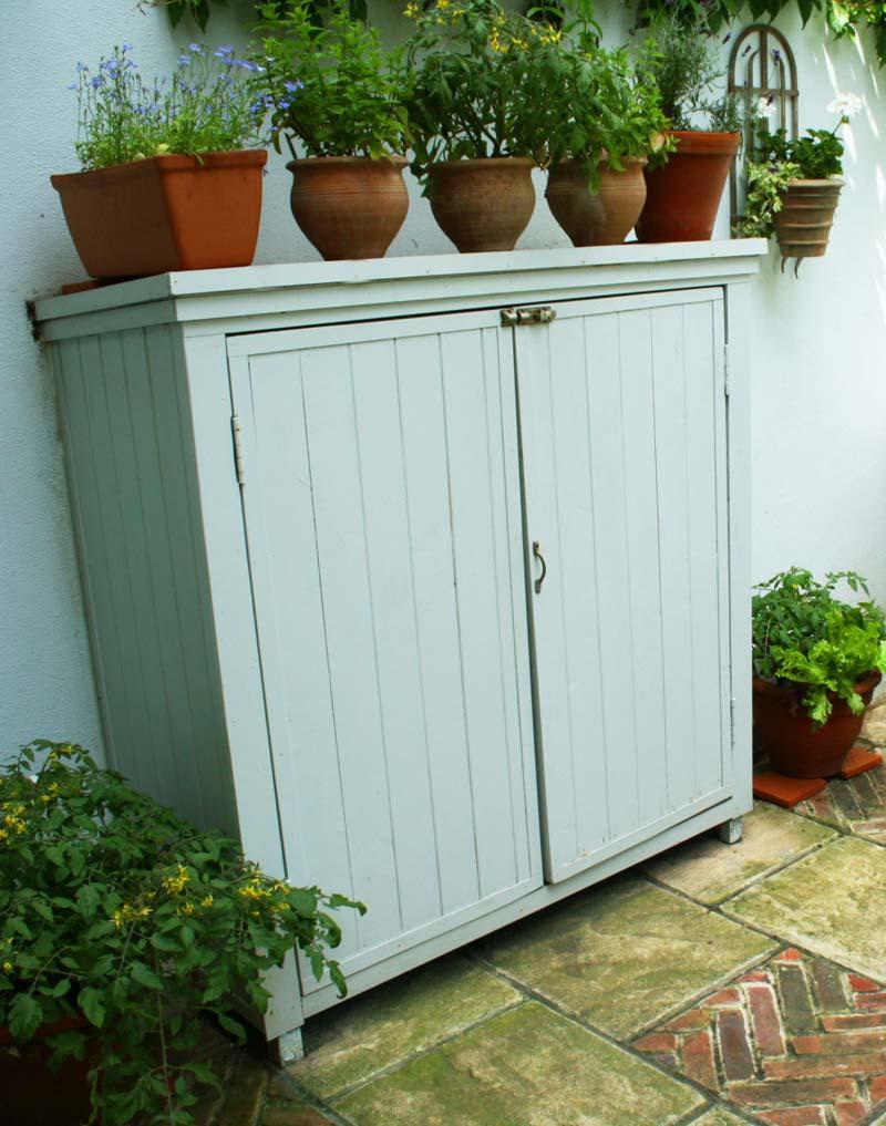 kleine tuin ontwerpen kleine romantische tuin terracotta potten op mintgroene kast
