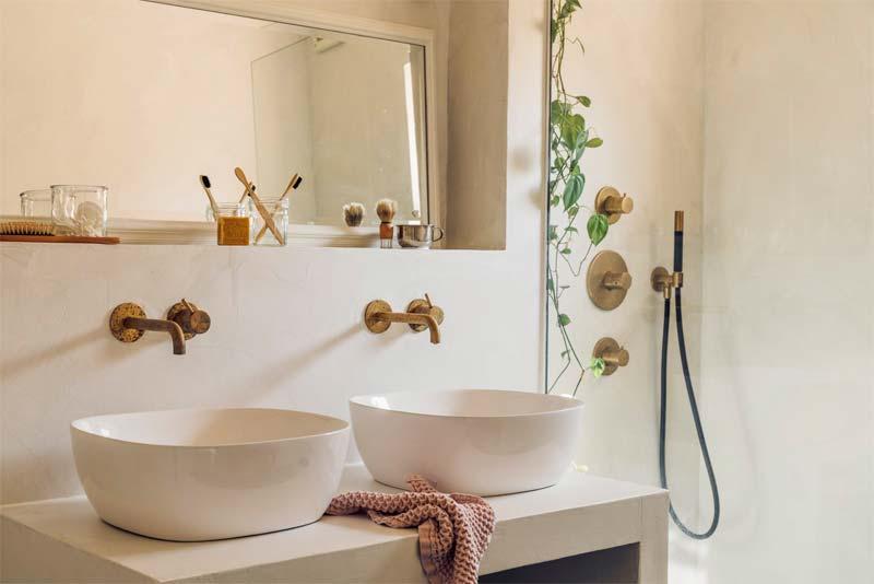 lichtgrijze beton cire muur en wastafelblad in badkamer met gouden kranen