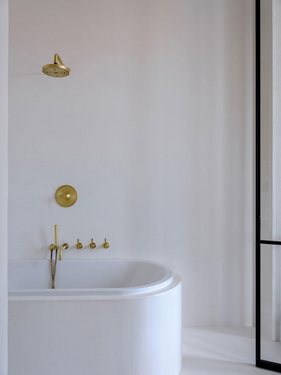luxe badkamer ensuite met witte pleisterwanden, gouden kraan en gouden douche