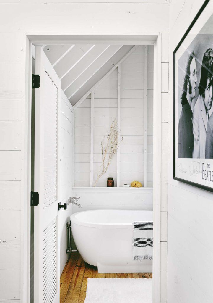 De ontwerpers van interieurarchitecten van Rauser Architects hebben om de mooie houten planken aan de wanden en plafonds van deze moderne landelijke badkamer wit te verven. Klik hier voor meer foto's.