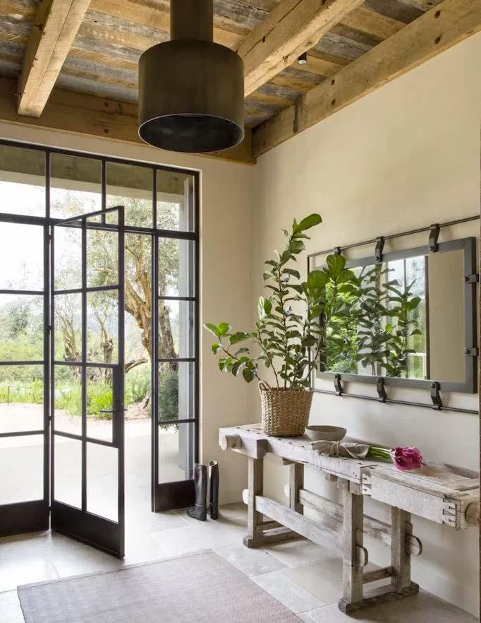 De mooie groene plant op de rustieke houten sidetabel maakt deze prachtige modern landelijke hal compleet. Ok, de stalen deur met het glas vormt hier natuurlijk wel de blikvanger!