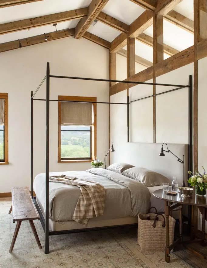 De ontwerpers van Jute heeft deze super mooie slaapkamer ontworpen, met onder andere een stalen hemelbed, een rustiek houten bankje aan het voeteneinde en een groot vloerkleed met een mooi patroon half onder het bed.