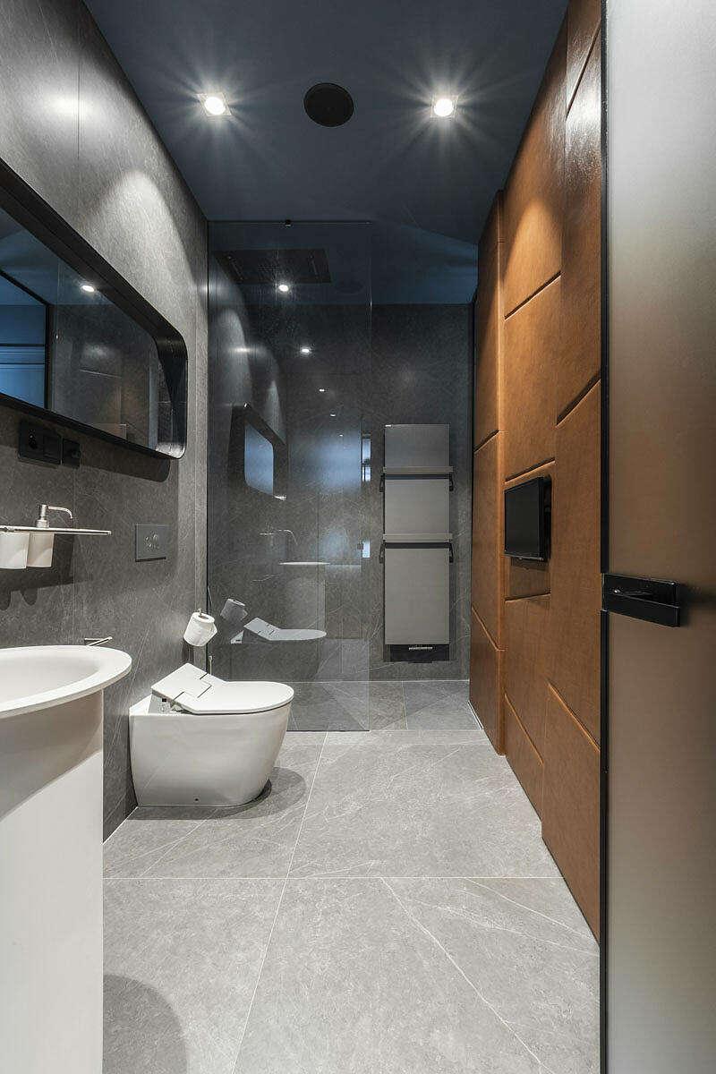 Moderne badkamer betonlook tegels en leren wandbekleding