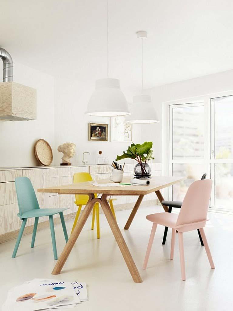 Moderne keuken met multiplex kasten, houten eettafel en pastelkleuren stoelen.