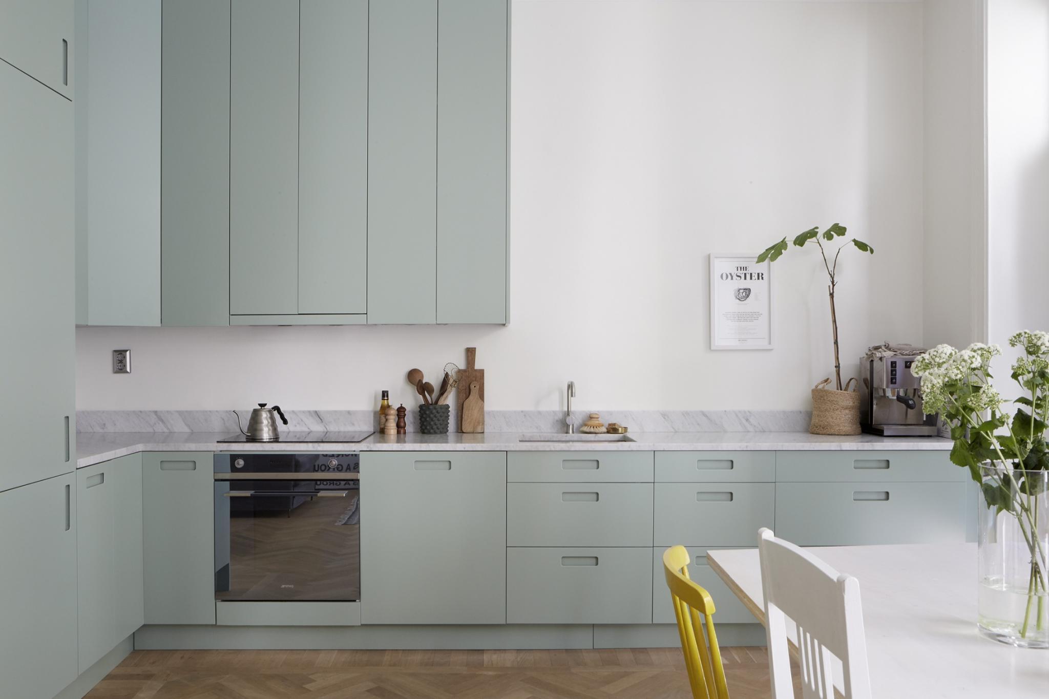 Moderne mintgroene keuken met een marmeren werkblad homease