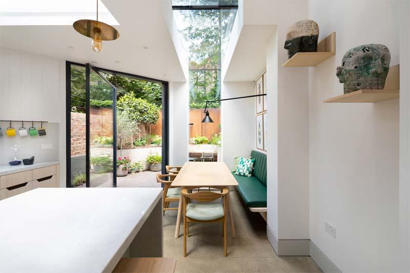 Fraher Architects heeft een rijtjeshuis in King's Cross in Londen gerenoveerd, met een uitbouw aan de achterkant bekleed met geperforeerd zwart metaal en een metalen trap.