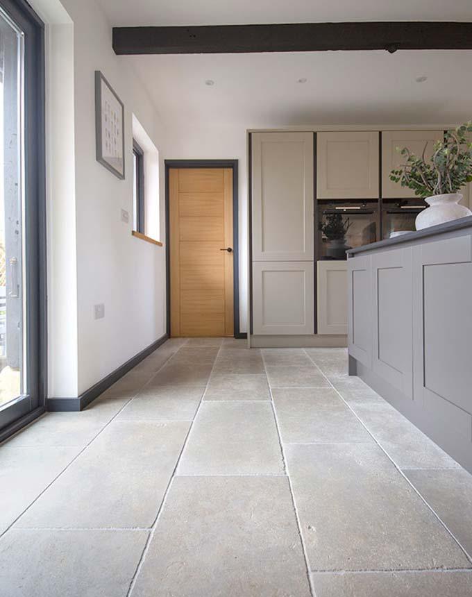 De lichte Clermont Gris kalksteen tegels van Mystonefloor.com staan prachtig in deze moderne landelijke keuken.