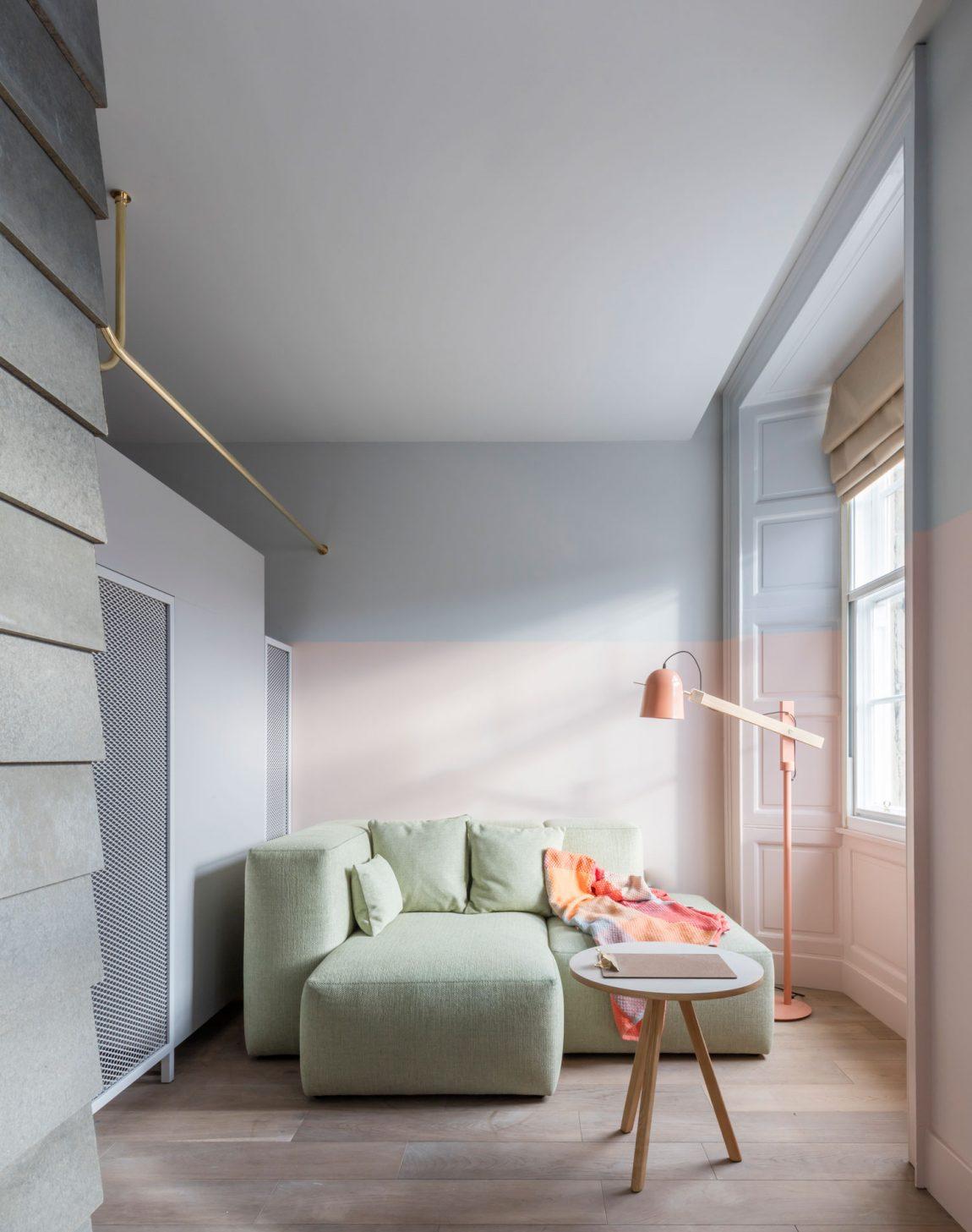 Hier zie je een van de kamers van het mooie Eden Locke hotel in Edinburgh, met een pastelroze muur en een superleuke pastelgroene bank.