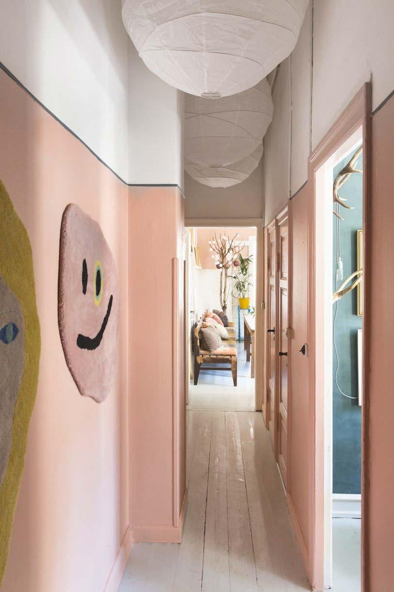 In deze hal is een hoge lambrisering geverfd in een mooie pastelroze kleur.