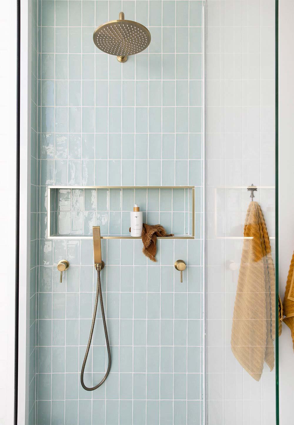 Super mooie badkamer met pastelblauwe tegels in de inloopdouche, gecombineerd met gouden accenten.