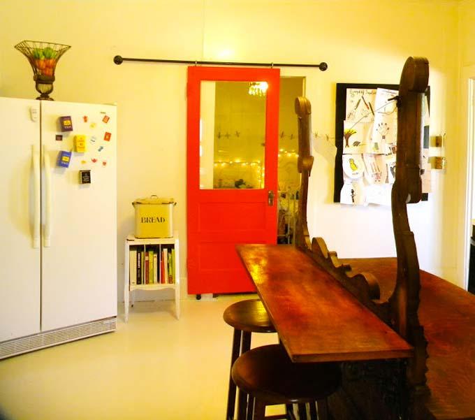 Voor het maken van een boerderij schuifdeur heeft Amy gebruik gemaakt van een mooie rode paneeldeur met glas.