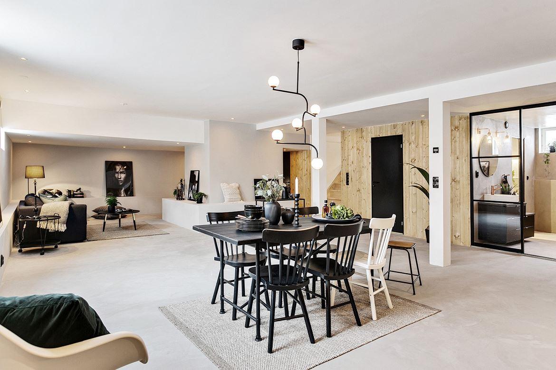 Sfeervolle woonkamer met betonlook gietvloer en grijze muren | HOMEASE