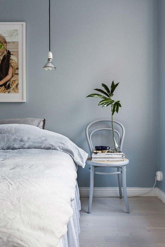 slaapkamer met blauwe muur en blauwe stoel als nachtkastje
