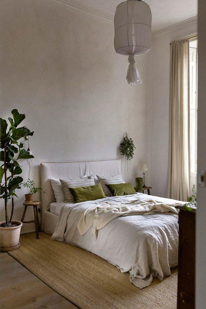 Mooie slaapkamer met mooi bedlinnen, jute vloerkleed en mooie planten