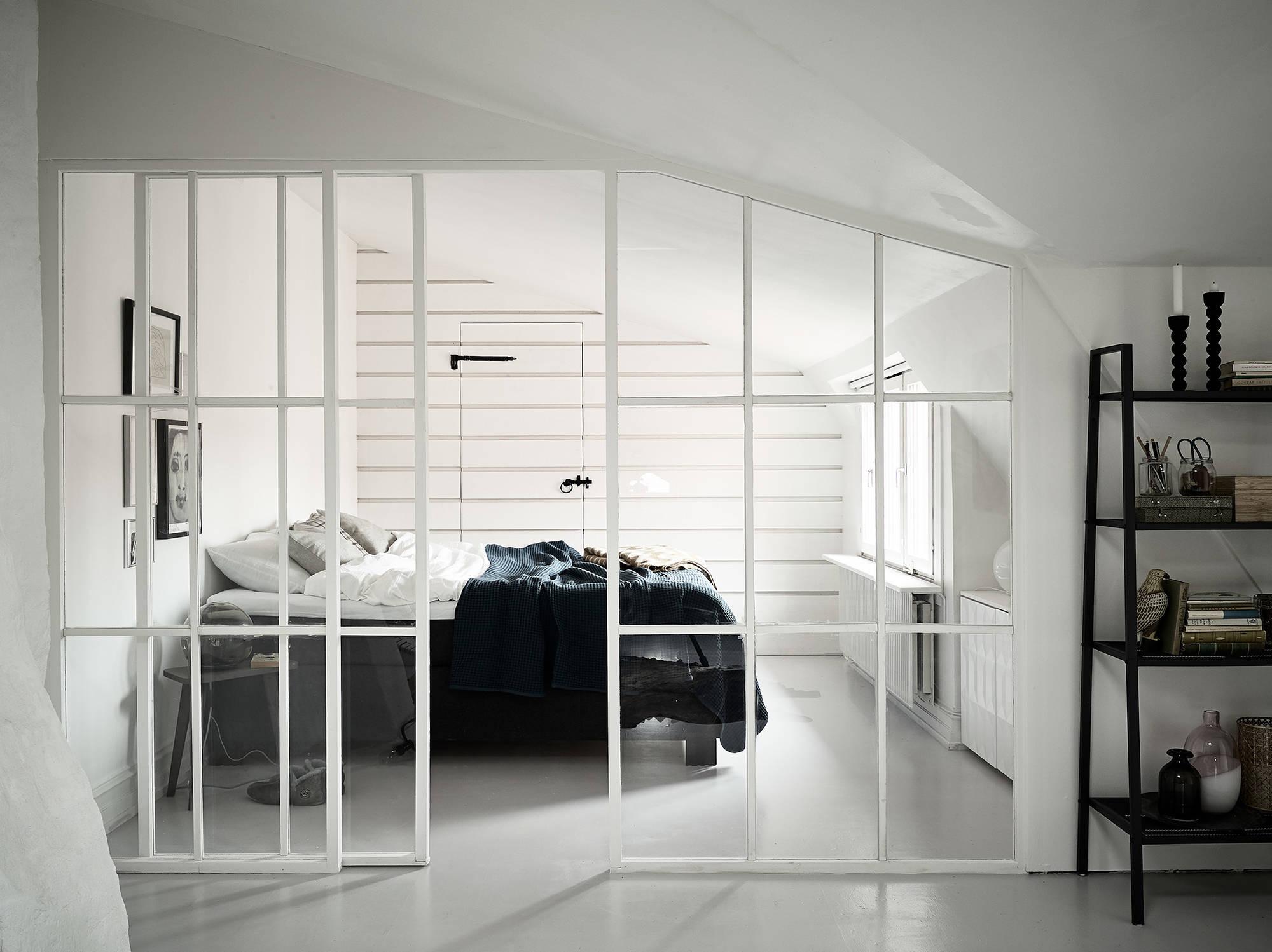 Slaapkamer met een glazen wand met stalen witte kozijnen