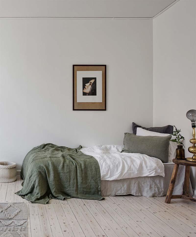 In deze super mooie slaapkamer is het bed gedecoreerd met een mooi olijfgroen linnen bedsprei en kussens.