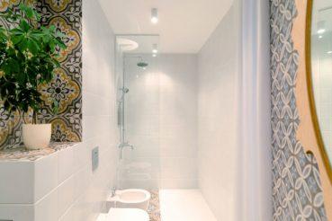 Smalle lange badkamer met een mooie tegelmix
