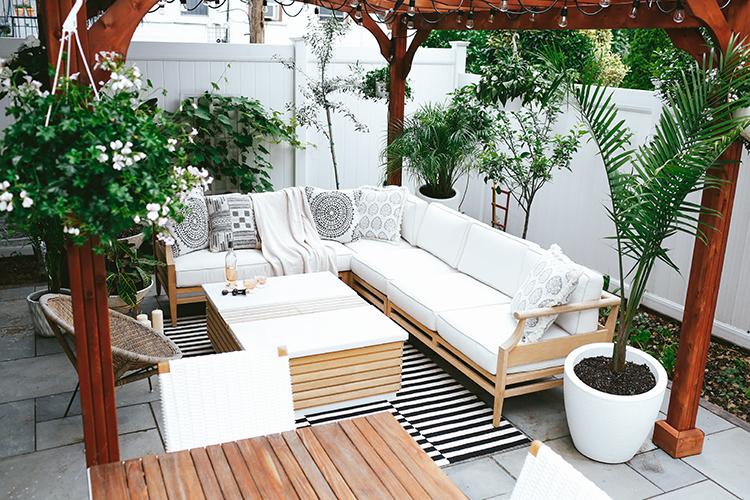 Helena van Brooklynblonde.com heeft een gezellige loungehoek met tuinkleed ingericht in haar tuin onder een grote houten pergola.