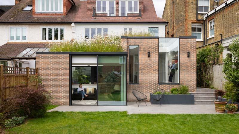 Fraher & Findlay heeft een uitouw aan de achterkant van een 20e-eeuws huis in Londen gebouwd met grote glazen wanden, glazen lichtstraat en een strakke glazen schuifpui.