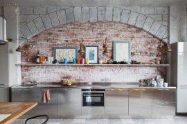 Unieke keuken met RVS kasten en bakstenen keuken achterwand