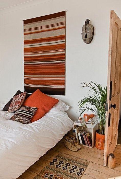 Klein vloerkleed aan de muur boven het bed