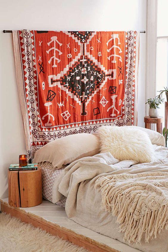 Groot vintage vloerkleed aan de muur boven het bed