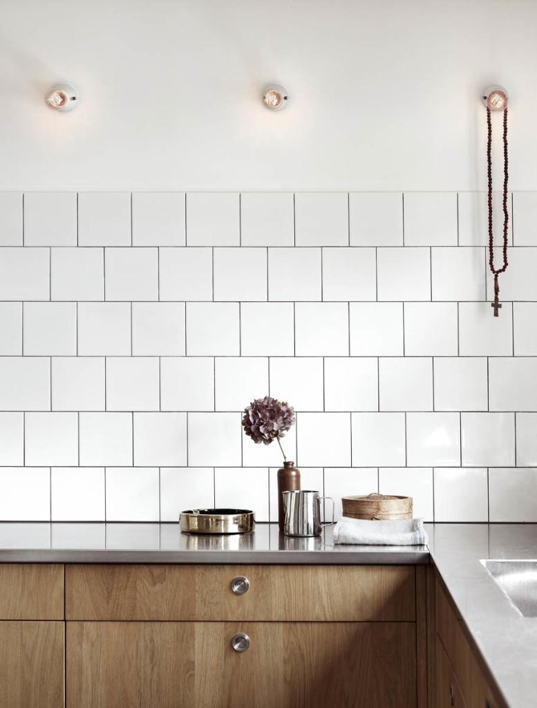 De keukenwand is betegeld met simpele witte vierkante tegels ...